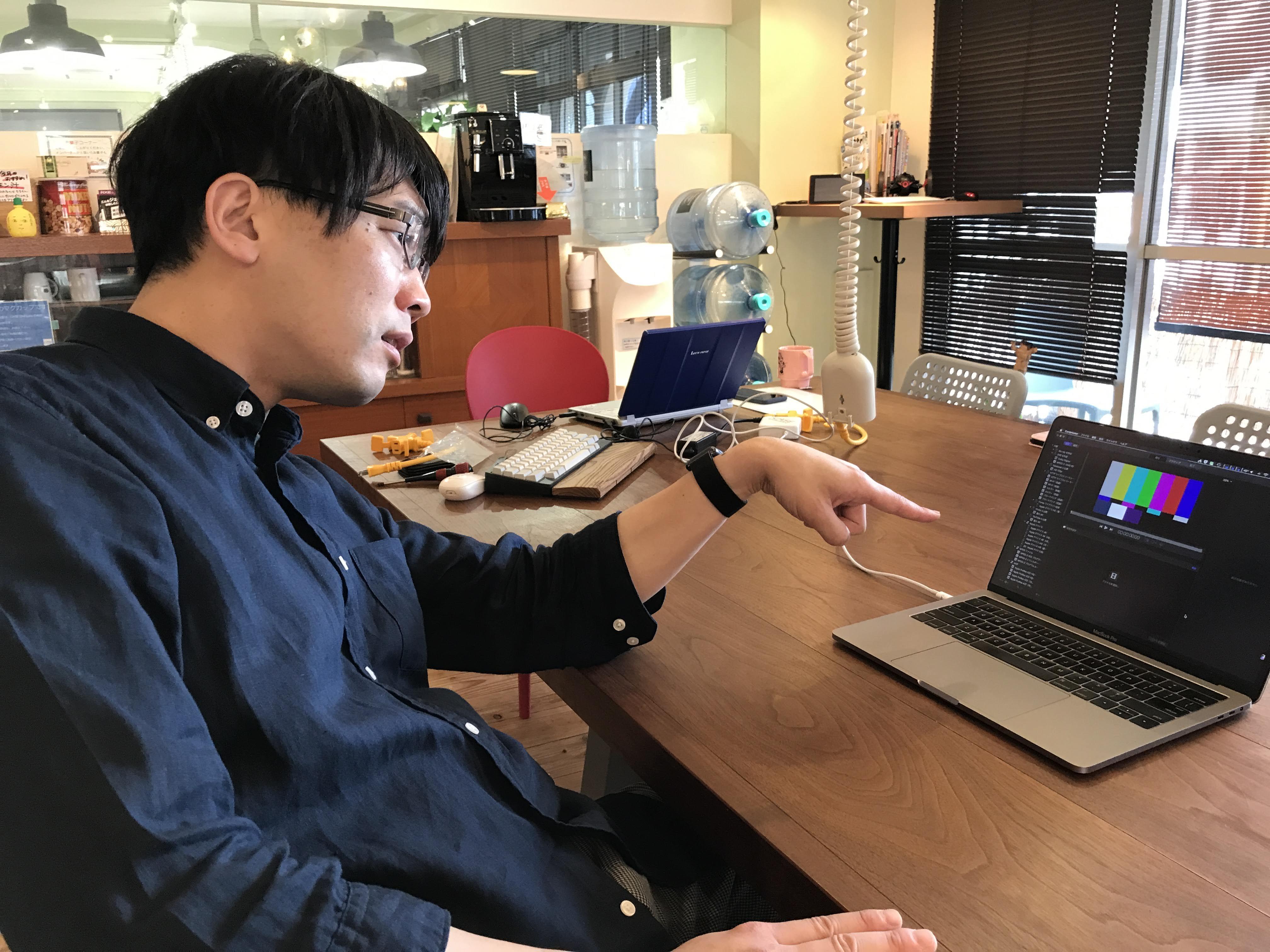 MacBook Proを指さす田中健一朗