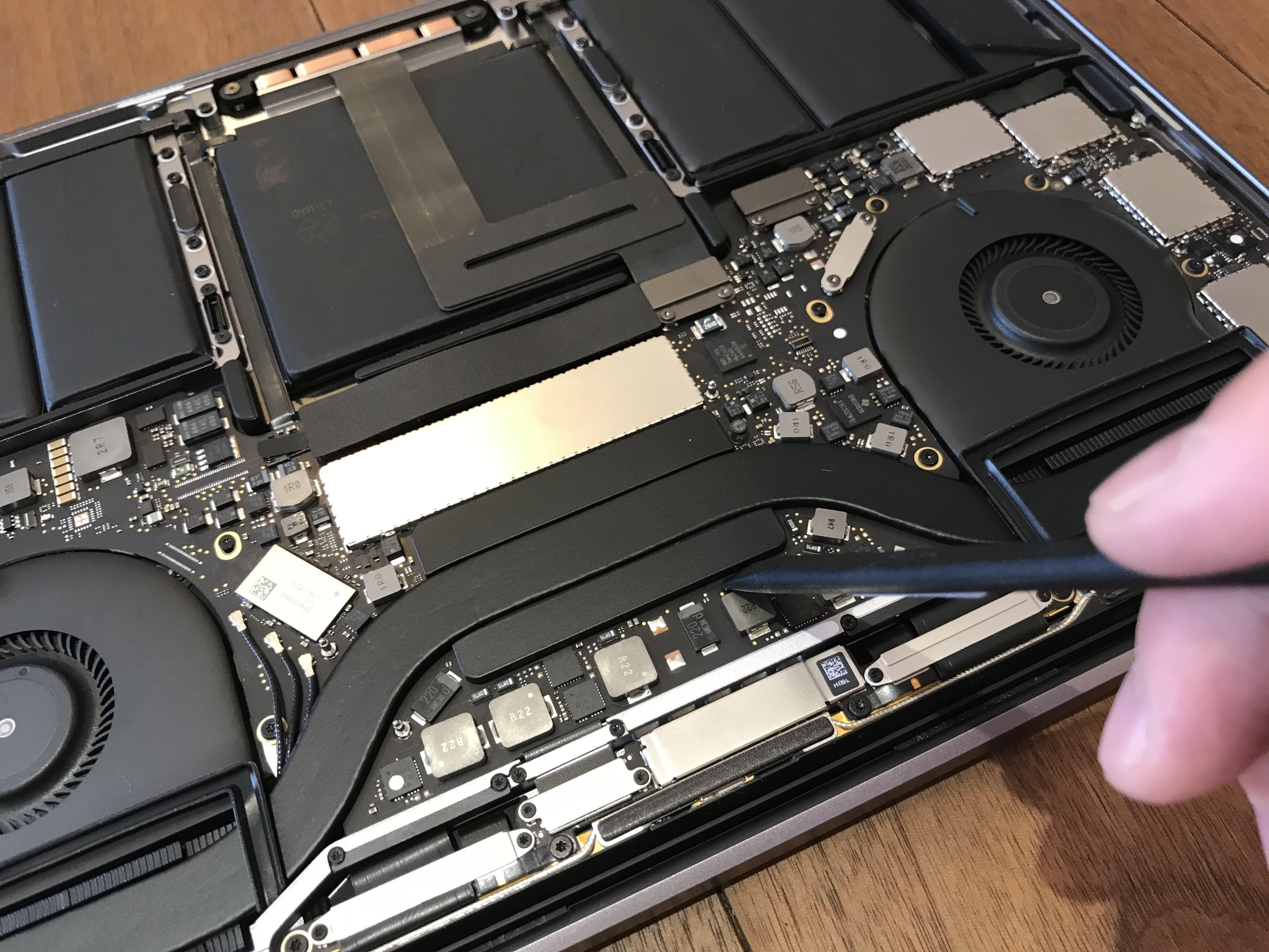 MacBook Proのヒートシンクをツールでこじ開けようとしている様子