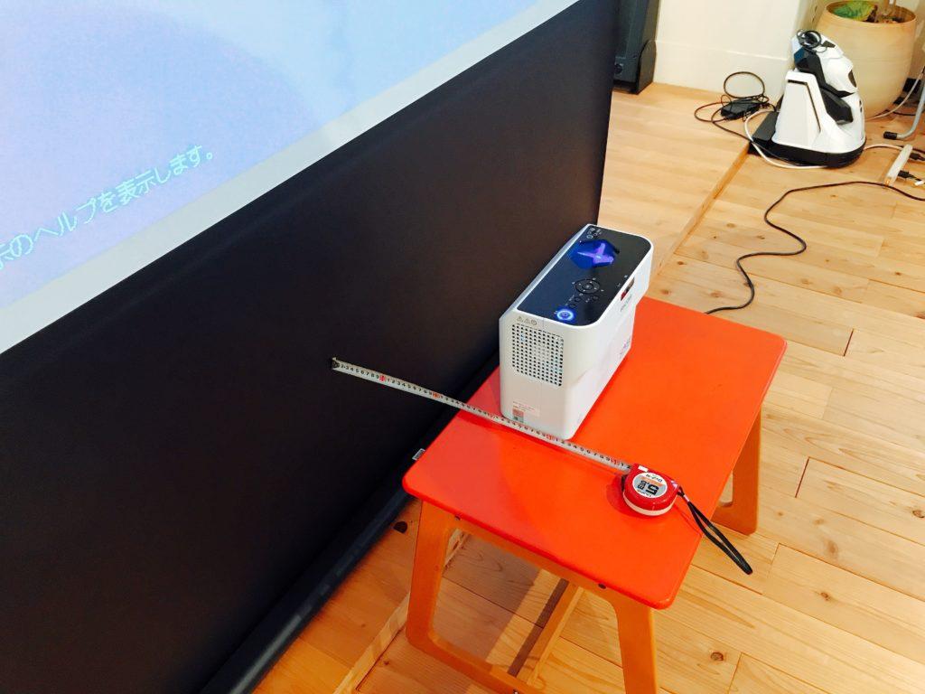 RICOH PJ WX4152とスクリーンの距離を測定している様子